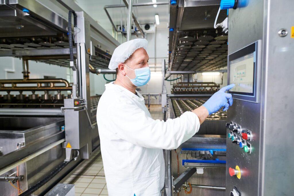 une personne masquée de l'agroalimentaire programme une machine de production