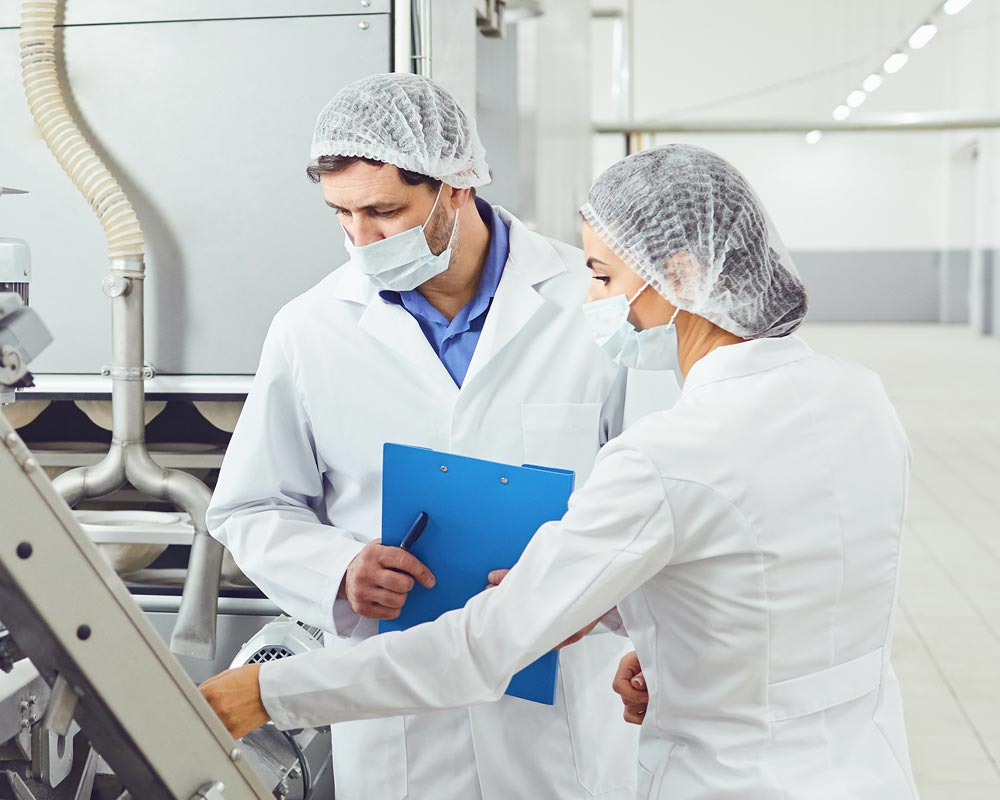 Deux personnes masquées de l'agroalimentaire contrôlent une machine de production